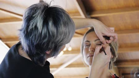 átalakítása : Female make-up artist tinting eyelashes of young attractive woman in large terrace with wooden roof. Slow motion.