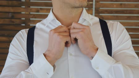 manşet : Close-up of young athletic man with dark blue suspenders zipping a button on his white shirt on a wooden wall background. Stok Video