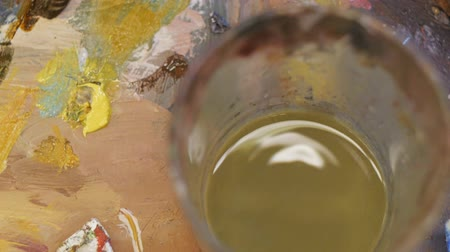 lijnzaad : Close-up of painting process. Drops of linseed oil drain from the spatula and drip into the glass.