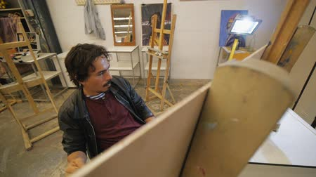 мольберт : Male bearded hispanic artist in black leather jacket paints with a brush on a canvas illuminated by a spotlight in art studio. High angle view. Стоковые видеозаписи