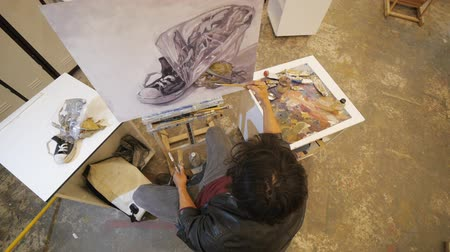 мольберт : Male hispanic artist in black leather jacket paints oil still-life on canvas sitting on chair in art studio. Similarity of the model and drawing. View from above shot.