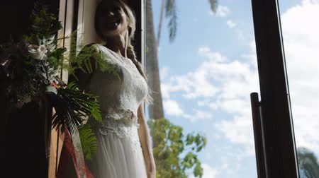 Beautiful caucasian female model in cream-colored brides wedding dress with bouquet in hands laughs standing at large glass door. Low angle view.