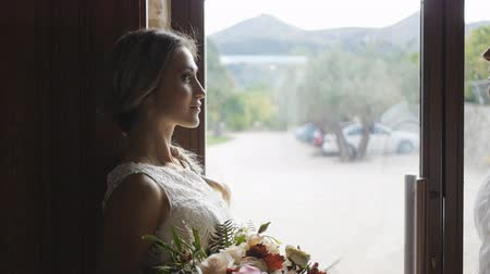 Athletic groom comes to slim blonde bride near large window. Guy and girl smiling looking to each other.