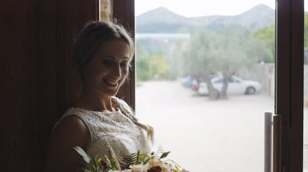 Portrait of beautiful caucasian female model in cream-colored brides wedding dress with bouquet in hands laughing standing at large glass door.