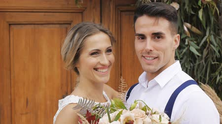 Slim blonde caucasian bride and athletic hispanic groom with a bright bouquet in hands smile on wooden door background outdoors. Close-up.