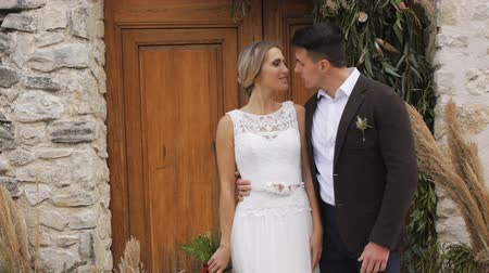 expat : Slim blonde caucasian bride and athletic hispanic groom with a bright bouquet in hands looking at each other on wooden door in wall of ancient castle background. Orbit shot. Slow motion.