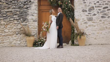 expat : Slim blonde caucasian bride and athletic hispanic groom with a bright bouquet in hands kissing looking at each other on wall with wooden door of ancient castle background.