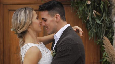 Slim blonde caucasian bride and athletic hispanic groom with a bright bouquet in hands kissing hugging on wooden door background outdoors. Close-up. Slow motion.