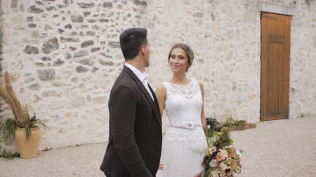 expat : Slim blonde caucasian bride and athletic hispanic groom go hand in hand stopping and kissing on wall of ancient castle background outdoors. Medium shot.