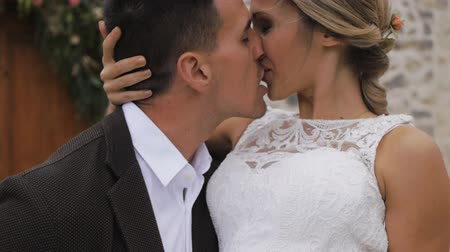 Athletic hispanic groom holding slim blonde caucasian bride in his arms kissing on ancient castle wall background outdoors. Close-up. Slow motion.