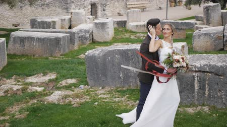 Slim blonde caucasian bride and athletic hispanic groom with flowers in hands kissing on big rectangular stones background. Ribbons of bouquet waving in the wind. Long shot.