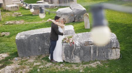 Slim blonde caucasian bride and athletic hispanic groom with flowers in hands kissing on big rectangular stones background. Long shot. High angle view. Stok Video