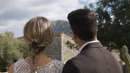 Slim blonde caucasian bride and athletic hispanic groom standing together looking at mountain near ancient castle. Back view. Close-up.