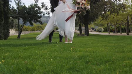 Bride in cream-colored brides wedding dress and the groom in dark blue trousers and brown shoes standing together on green grass. Ribbons of bouquet waving in the wind.