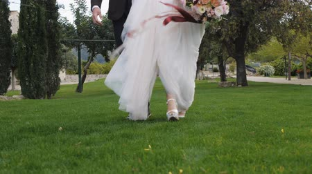 Bride in cream-colored brides wedding dress and the groom in dark blue trousers and brown shoes walking together on green grass. Low angle view. Stok Video