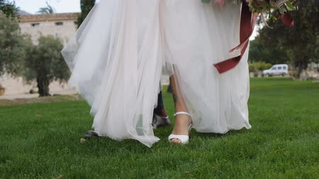 parte : Bride in cream-colored brides wedding dress and the groom in dark blue trousers and brown shoes walking together on green grass. Low angle view. Pan shot.