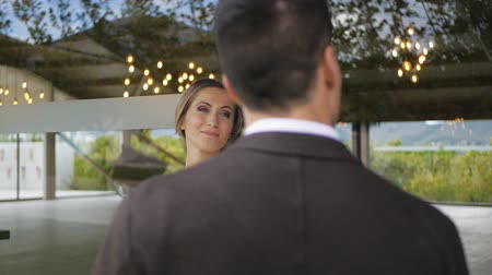 multinational : Slim blonde caucasian woman attentively looking at athletic hispanic man in black jacket on large glass window background. Slow motion. Medium shot. View over the shoulder.