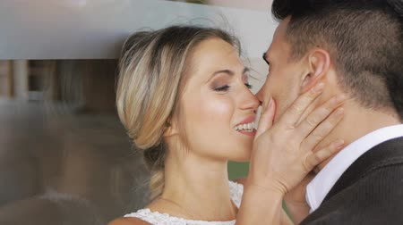 Attractive blonde slim woman and handsome athletic man in black jacket kissing looking at each other on large glass window background. Close-up shot. Slow motion.