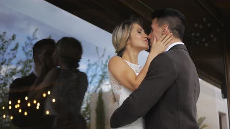 Pretty blonde caucasian woman and handsome athletic hispanic man in black jacket kissing hugging on large glass window background. Slow motion. Medium shot. Stok Video