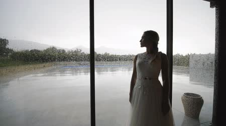 Pretty blonde woman in white dress standing near large window with raindrops. Slow motion. Medium shot.