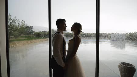 Pretty blonde woman in white dress and handsome hispanic man in white shirt and suspenders looking at each other near large window with raindrops. Slow motion. Medium shot.