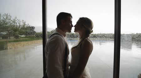 Pretty blonde woman in white dress and handsome hispanic man in white shirt and suspenders rubbing their noses near large window with raindrops. Slow motion. Medium shot.