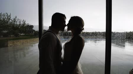Silhouettes of pretty blonde woman in white dress and handsome hispanic man in white shirt and suspenders rubbing their noses near large window with raindrops. Slow motion. Medium shot. Stok Video