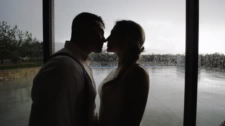 Silhouettes of pretty blonde woman and handsome hispanic man kissing near large window with raindrops. Medium shot.