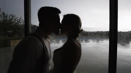 Silhouettes of pretty blonde woman and handsome hispanic man kissing near large window with raindrops. Medium shot. Slow motion. Stok Video