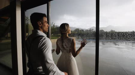 Handsome athletic hispanic man coming to pretty blonde woman near large window with raindrops. Medium shot.
