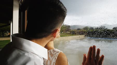 multinational : Handsome athletic hispanic man coming to pretty blonde woman kssing near large window with raindrops. Close-up.