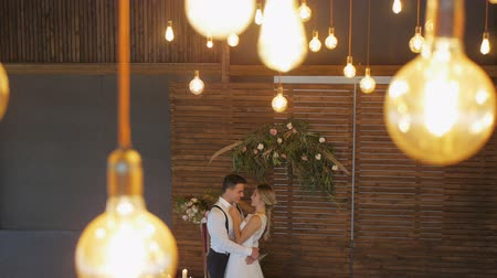 Blonde caucasian bride and athletic hispanic groom hugging looking at each other in wooden terrace on vintage bulbs background. High angle. Long shot.