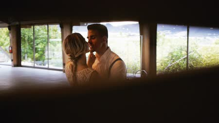 View through the crack of Blonde caucasian bride and athletic hispanic groom smiling looking at each other in wooden terrace on vintage bulbs background. Medium shot.