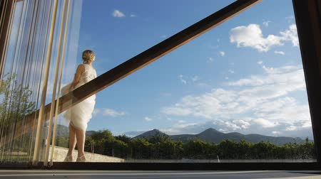 Bride holding the hem of the dress in her hands and the groom in in white shirt and suspenders take turns outside the window against the blue sky. Stok Video