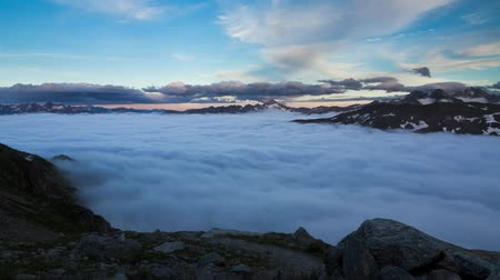 švýcarský : Time lapse of a sea of clouds in the valley at sunset on top of the Furkapass in Switzerland