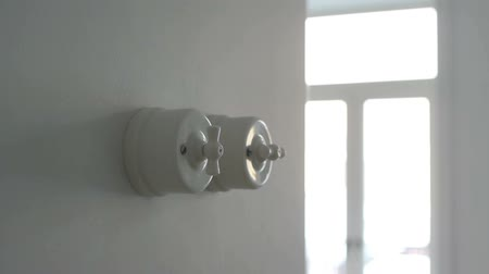 A man hand turning on and off a light switch in a house Vídeos