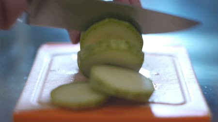 Hand cutting squash in a kitchen