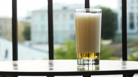 A glass of beer with high foam on the table on the balcony on a summer day Vídeos