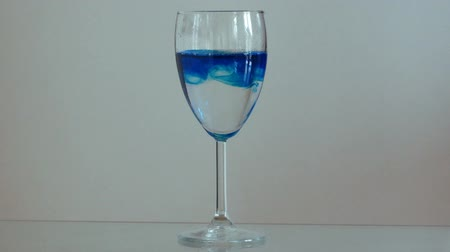 On the glass table is a glass of water, in which a blue liquid is bred. Vídeos