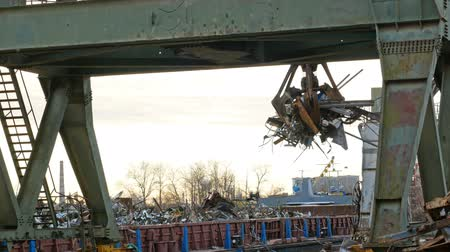 River port cranes load scrap metal into wagons