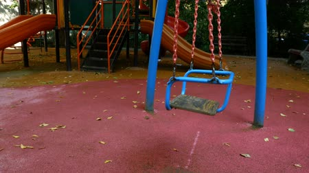 recess : Empty childrens swing on chains on an empty playground