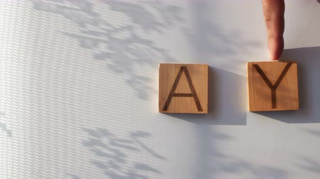 The word DAY is laid out in wooden letters Vídeos