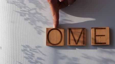 The word HOME is laid out in wooden letters Vídeos