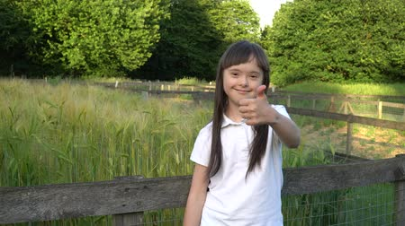 Down syndrome girl giving thumbs up and smiling in the park