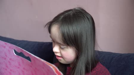 Down syndrome girl is drawing at home