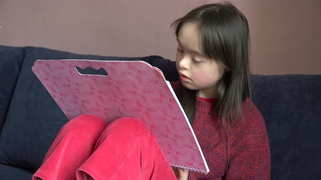 pré escolar : Down syndrome girl is drawing at home