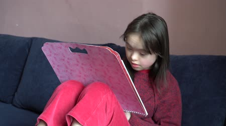 детский сад : Down syndrome girl is drawing at home