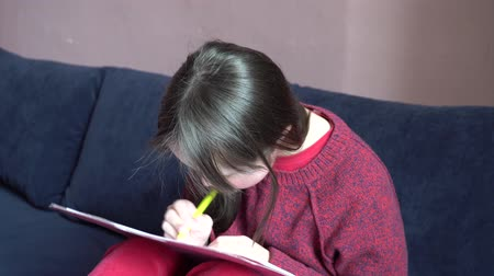 školka : Down syndrome girl is drawing at home