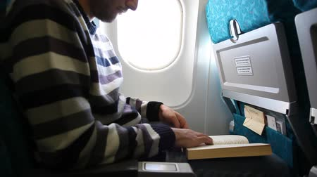 книги : the man who reads books on the plane Стоковые видеозаписи