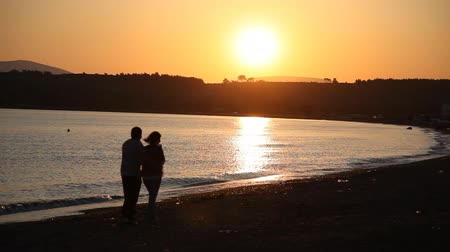 закат : happy couple walking at beautiful sunset